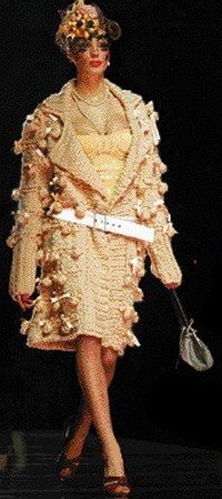 Here, one of Galliano's girls in a big, cozy ribbon-bedecked sweater, a wartime-style, all-in-one undergarment, fruit-bedecked, veiled hat and platform shoes.