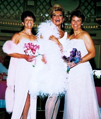 Yolanda Cellucci, middle, owner of Yolanda's bridal emporium, dresses a lesbian couple in Steven Yurich, left, and Yoly Munoz, right, at The Pink Event sponsored by Bloomingdale's.