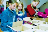 Ashley Penessa and Shannon Kelly pack boxes of beauty products.