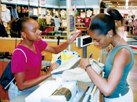 Victoria Richardson tries her hand at ringing up a sale from fellow Boys & Girls Club member Kirsten Grimes during their recent participation in Camp Old Navy at Opry Mills in Nashville.