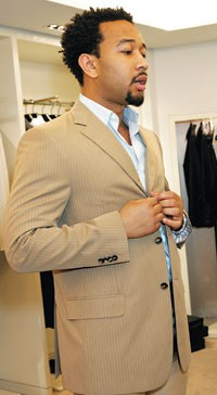 John Legend gets fitted for a suit at the Valentino store.