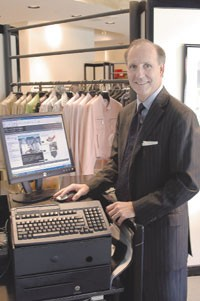 Stanley Korshak owner Crawford Brock with a flat-screen Dell.