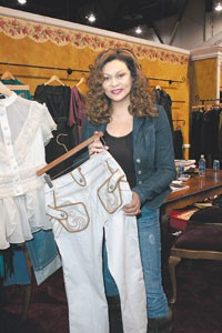 Tina Knowles holds House of Deréon tan jeans with piping and embroidery.