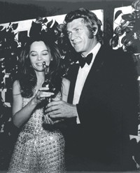 A photo of Caron wearing sequined overalls by Marc Bohan for Christian Dior, presenting Steve McQueen with a Golden Globe in 1969.