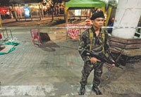 A Thai soldier stands guard near the scene of one of the explosions in downtown Bangkok.
