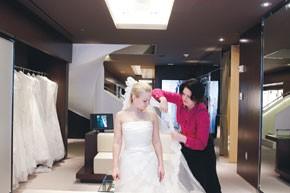 Sarah Burton helps a bride with her train.