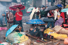 Local people wait to be transported to safe areas as the injured lay in the open air and rain falls on Tuesday.