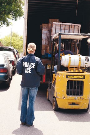 ICE officials load confiscated apparel into a truck.
