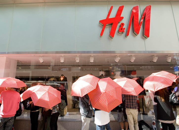 Hong Kong shoppers use umbrellas to shield themselves from the sun as they wait to buy Comme des Garçons.