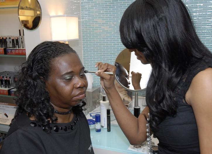 A beauty adviser applies eye shadow.