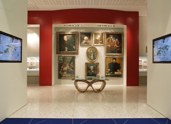 "Portraits in the gallery and a glass-top ""eyeglasses"" table."