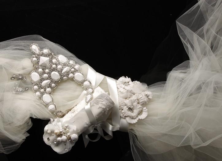 Nicole Miller's crystal earrings, Reem Acra's silk-covered rhinestone and crystal necklace, Oscar de la Renta's silk satin and tulle clutch with Swarovski crystals, Junko Yoshioka's silk and rhinestone belt and Romona Keveza's silk tulle veil.