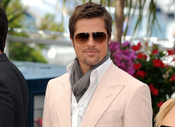 Brad Pitt in a Tom Ford pastel two-piece suit, white shirt and a gray cashmere scarf wrapped around his neck and tucked into the shirt.