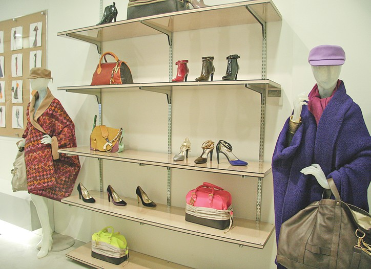 Footwear and handbags flanked by blanked coats.