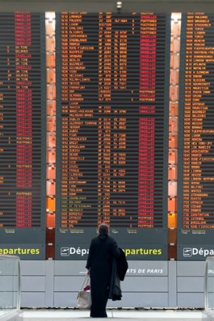 A traveler scans the canceled flights at Charles de Gaulle airport.