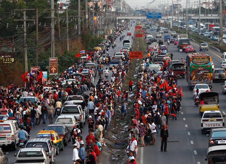Anti-government protesters block a main road leading into Bangkok.