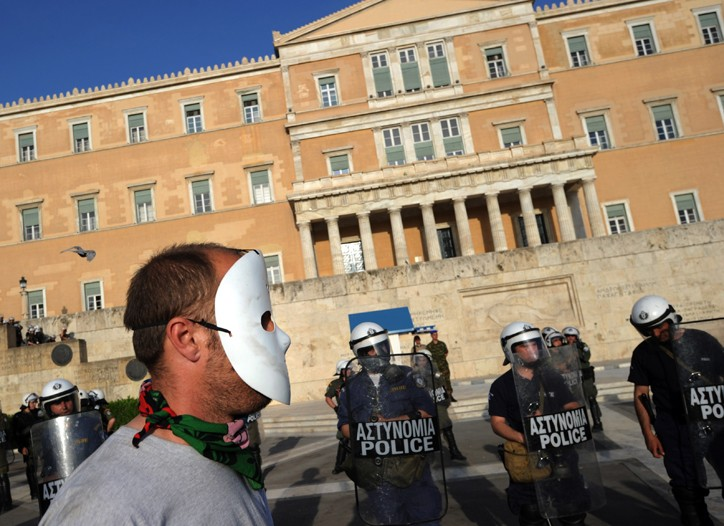 A masked protestor looks at a police cordon in front of the Greek Parliament in central Athens.
