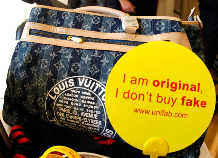 """The slogan, """"I am original, I don't buy fake,"""" is displayed on a counterfeit Louis Vuitton luxury handbag by French Customs officers before a destruction operation in Cannes last year."""