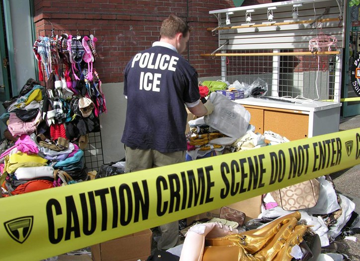 An ICE agent searches one of eight Bay Area retailers suspected of selling counterfeit apparel and accessories.
