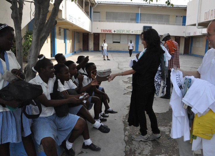 llan Ellinger and Lauren Perry, director of communications for Fashion Delivers, distribute donated product to young women at an orphanage in Cité Soleil, Haiti.