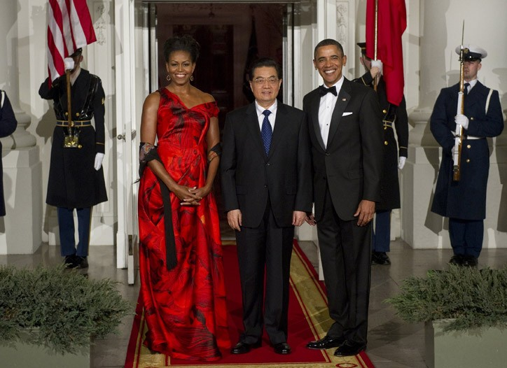 Michelle Obama in a red, petal-print organza gown by Alexander McQueen