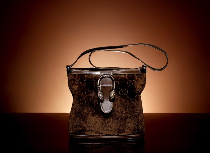 """A double-G velvet shoulder bag from the early Seventies with leather trim and an enameled """"tiger heads"""" ornament."""