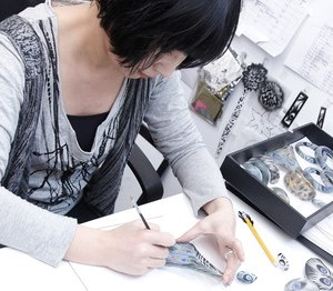 A bangle is hand-painted in Alexis Bittar's workshop.