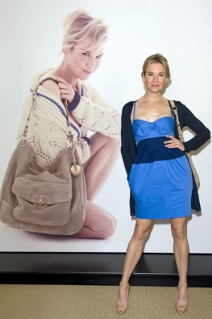 Renée Zellweger stands in front of her likeness with the charity bag.