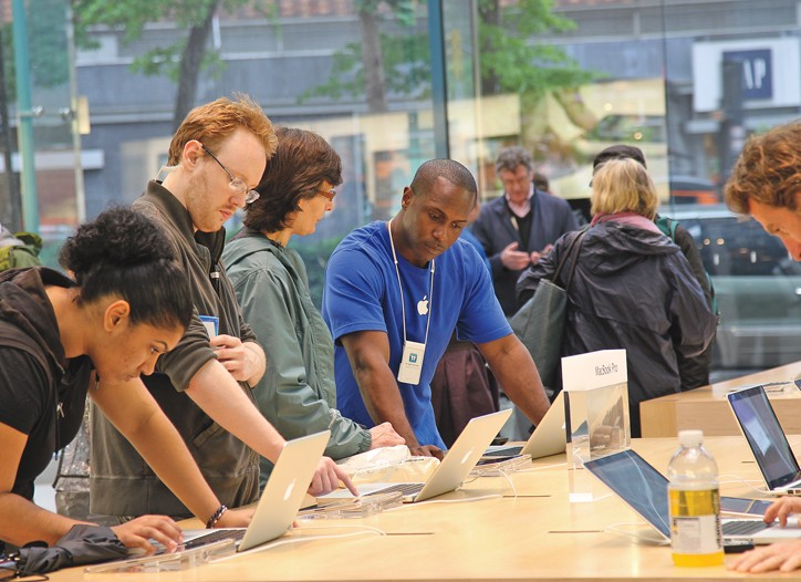 Customers being helped at an Apple store.