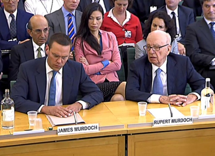 Wendi Murdoch sits behind James Murdoch and Rupert Murdoch.