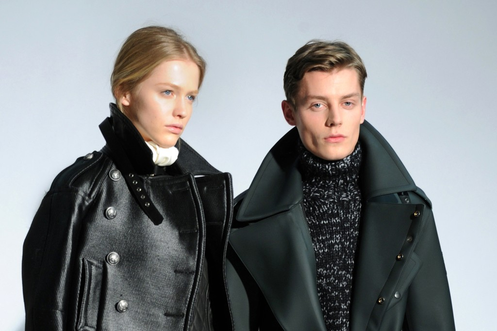 Her: A Topper jacket over a sleeveless biker gilet and a wrap trouser skirt. Calfskin bag and the leather boots have rubber soles. Him: PVC dispatch rider's coat with a wool, cashmere and angora mix sweater in marled yarn, and a biker equestrian boot.