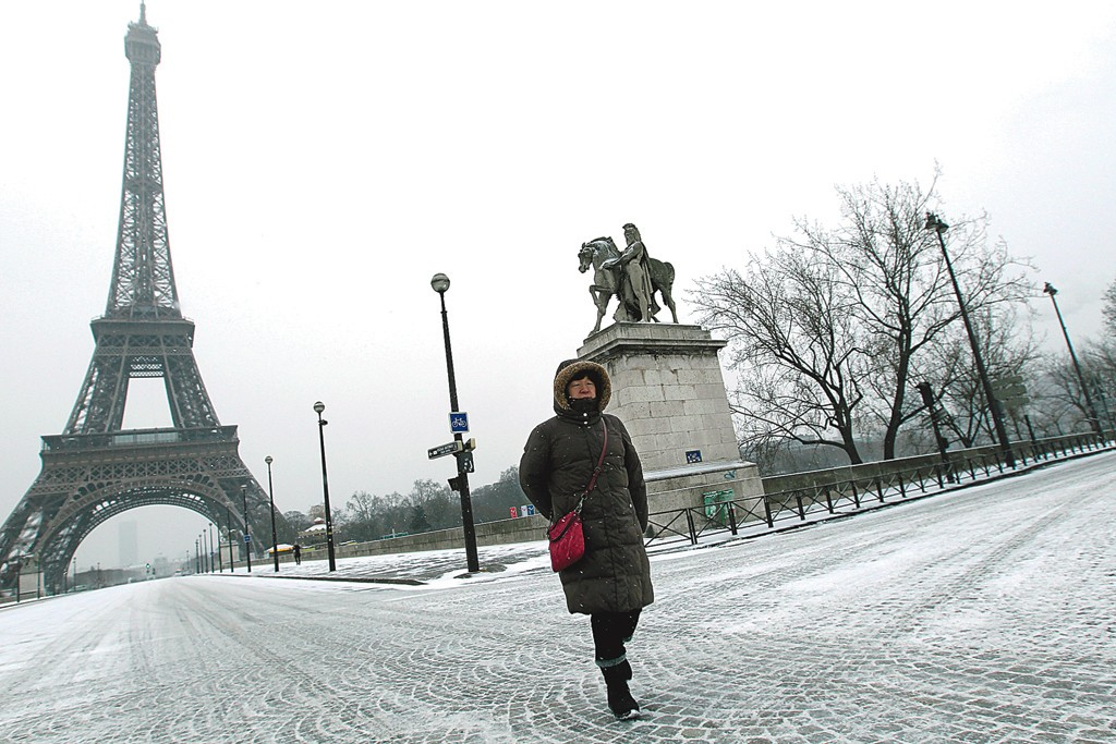 A toursit walks in front of the Eiffel Tower during snow fall.