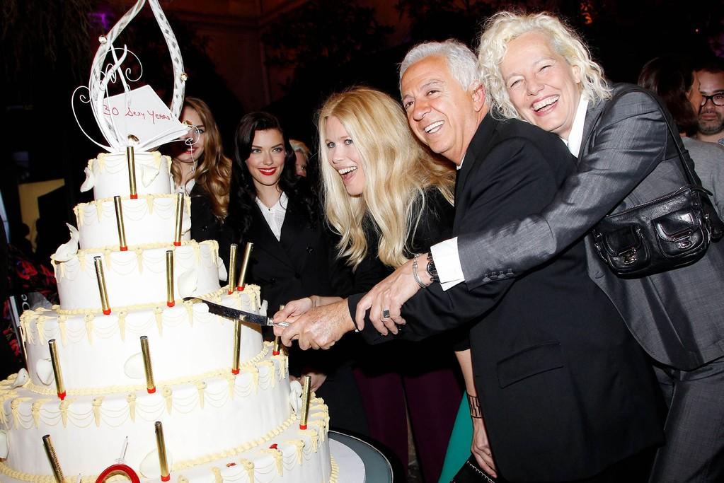 Claudia Schiffer, Paul Marciano and Ellen von Unwerth cut the birthday cake.