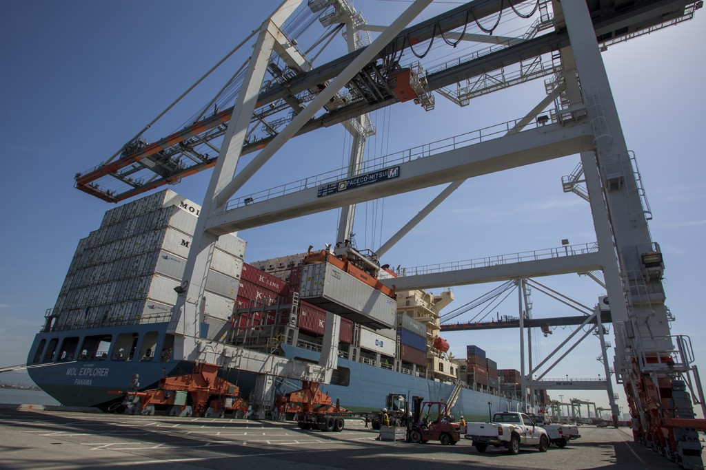 A crane unloads crates from a ship docked at the Port of Oakland.