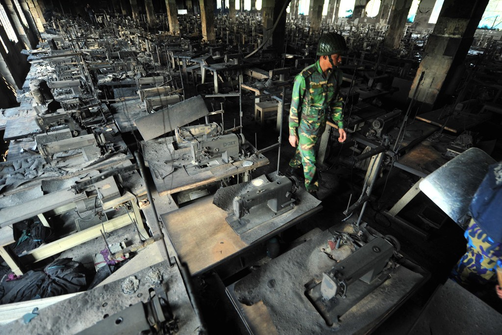 Bangladeshi Army personnel walk through rows of burnt sewing machines after a fire in the nine-story Tazreen Fashion plant.