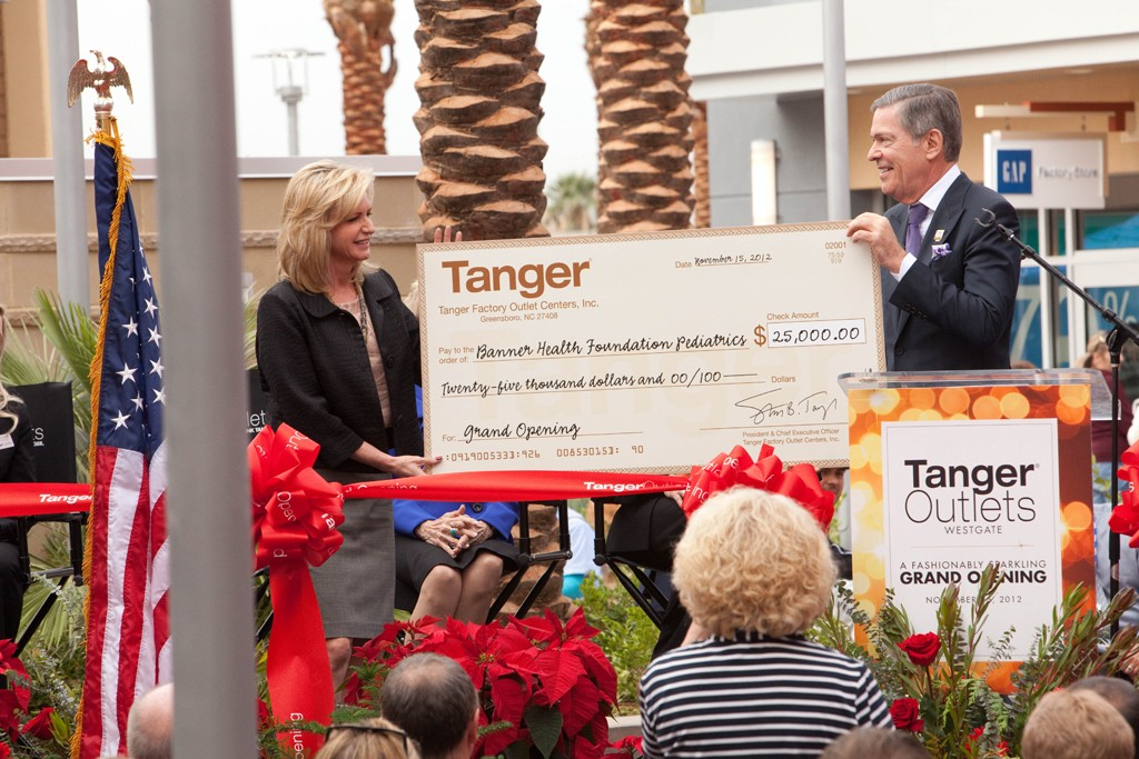 At the opening of Tanger Outlets, Westgate, in Glendale, Ariz., Steve Tanger presents a check to Andy Kramer Peterson, president and ceo of the Banner Health Foundation.