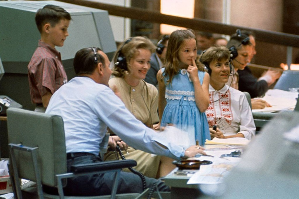Astrowives Pat White (right) and Pat McDivitt (left) and the Whites' children, Bonnie and Eddie III, visit Mission Control and sit with flight director Chris Kraft, during Gemini 4 (during which Ed White performed the first U.S. spacewalk), June 1965.
