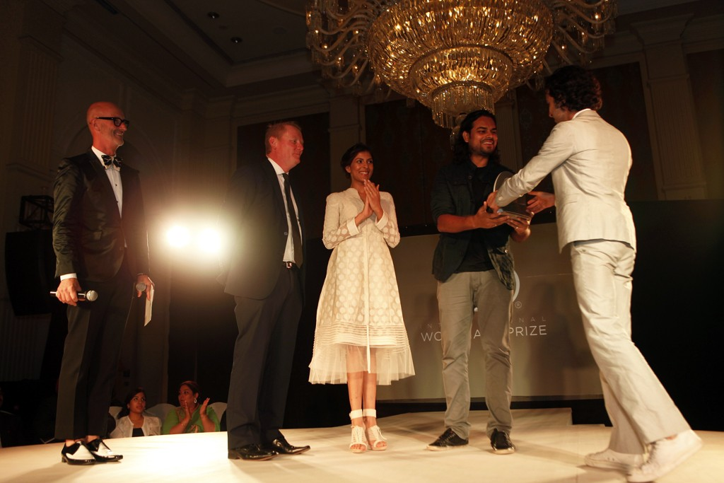 Simon Lock and Imran Amed presenting the International Woolmark Prize to Rahul Mishra.