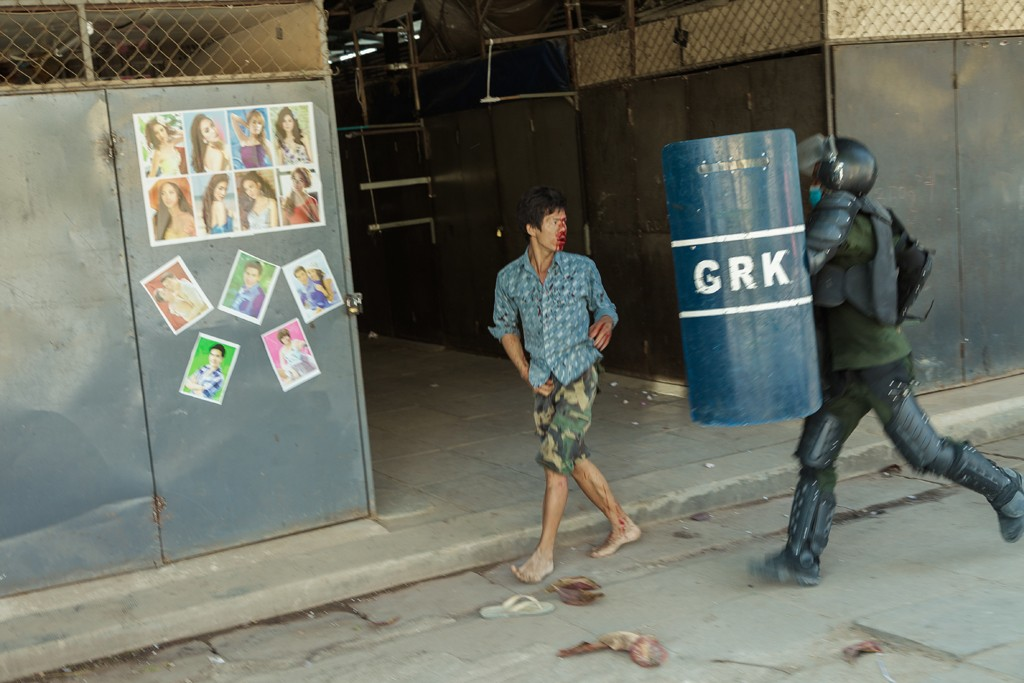 A badly wounded man tries to escape police after a raid inside Veng Sreng market in Phnom Penh on Friday.