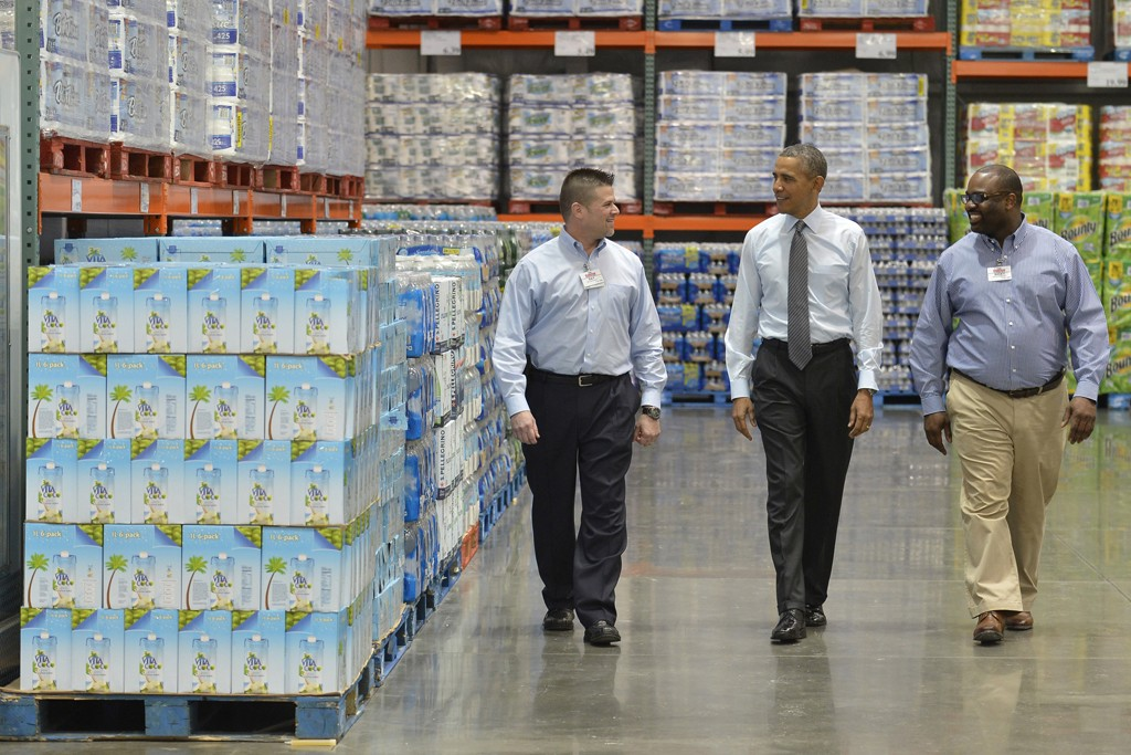 President Barack Obama is escorted by Costco employees Ray Quevedo and Rickey Banner while touring the store Jan. 29 in Maryland.