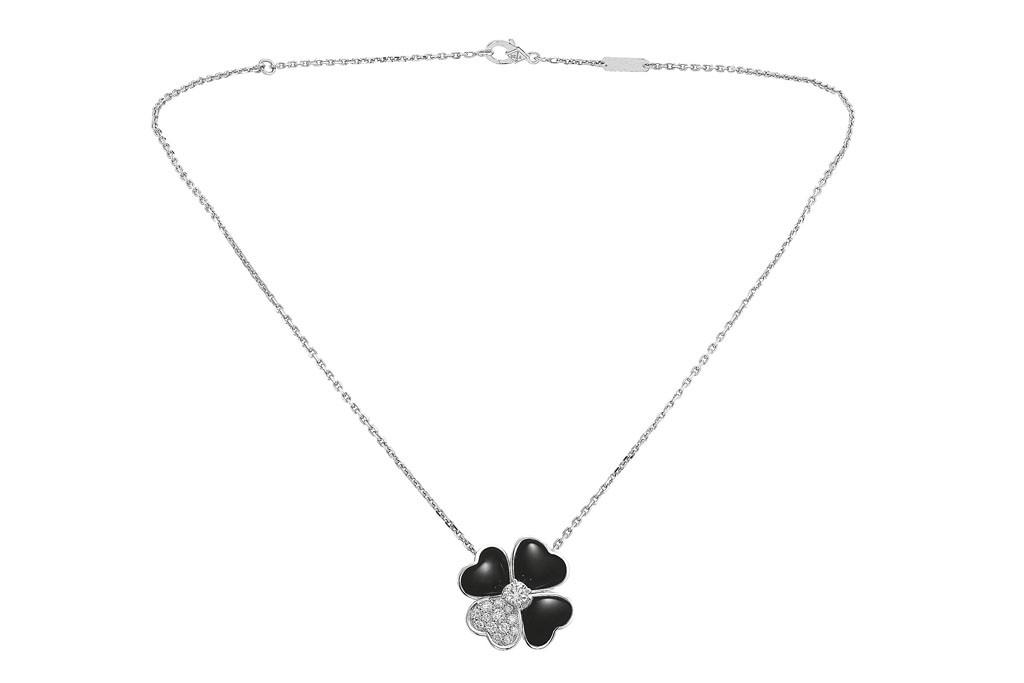 Van Cleef & Arpels' Cosmos medium model clip pendant in white gold, onyx and diamonds.