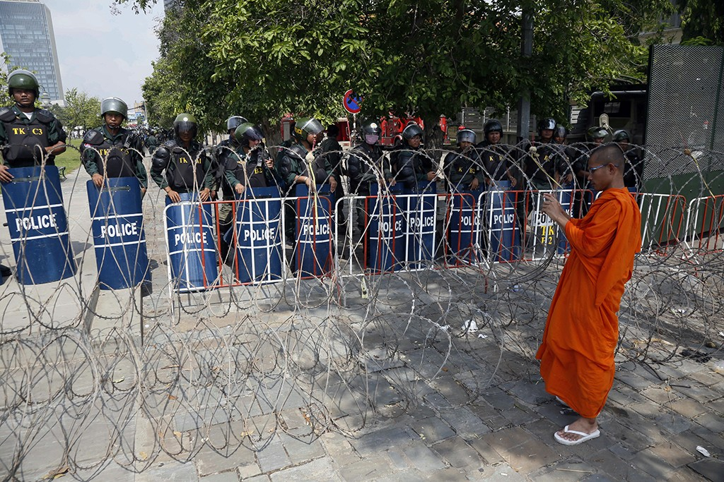A Buddhist monk takes a photo of riot police standing at Freedom Park in Phnom Penh, Cambodia.