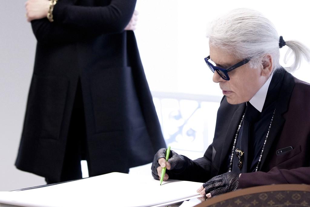 Delphine Arnault observes Karl Lagerfeld sketching.