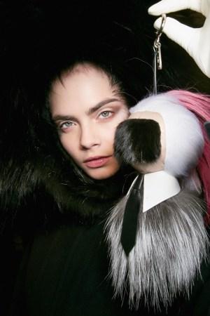Cara Delevingne holding the Karlito charm.