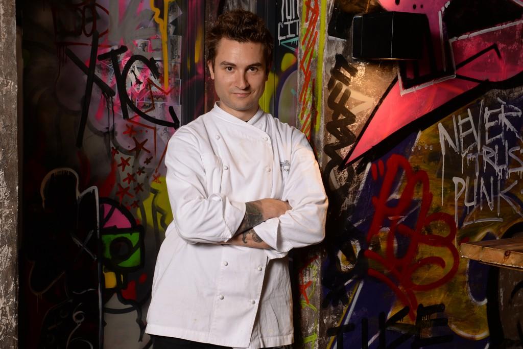 Alex Stupak against the graffitied interior of Empellón Al Pastor.
