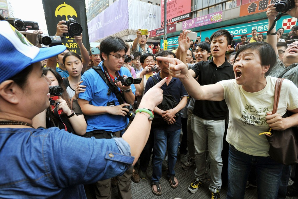 A pro-democracy protester has a heated exchange with a person opposed to the movement.