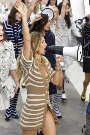 """Gisele, a vision in a sexy beige-and-white cardigan, led the raucous finale: a dazzling """"protest"""" along Chanel Boulevard of almost 90 models wearing Karl Lagerfeld's flamboyant spring creations."""
