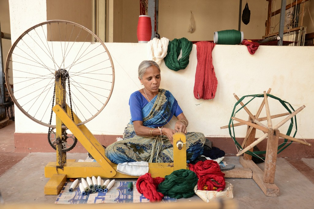 An Indian artisan transferring weft threads to large spools.