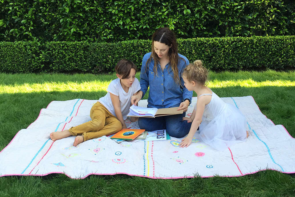 Jenni Kayne with her children Tanner and Ripley on a quilt she designed for Pottery Barn Kids.