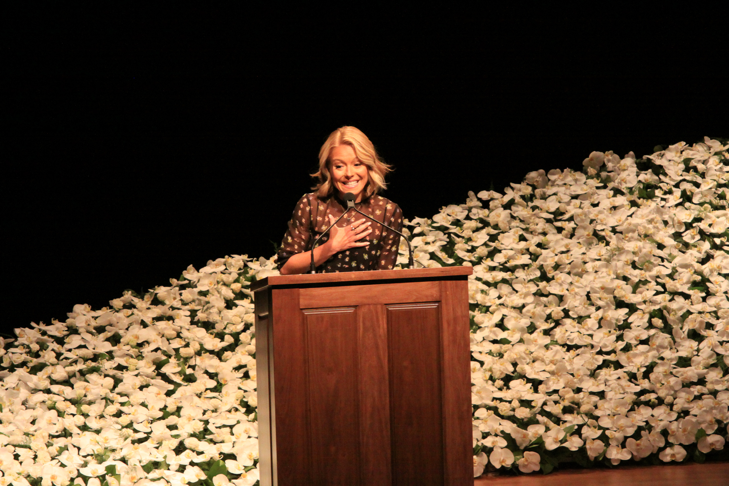 Kelly Ripa with the wave of orchids behind her at the memorial service for Dr. Fredric Brandt.